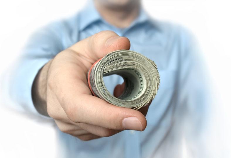 Man-Handing-Over-Roll-of-Dollars-1024x702.jpg